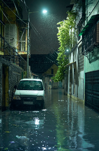 Lansdowne, Kolkata, 05/21/2020 : Excess rain caused flooding of a narrow lane, inside a residential locality on the day, the super cyclone Amphan caused havoc in Kolkata. Heavy rain associated with massive storm flooded many areas of the city. Shot at night, in street light.