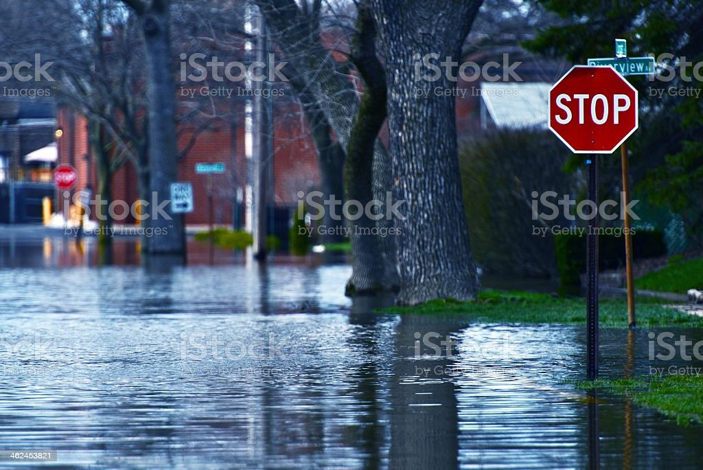 Flooded residential street at a stop sign Flooded Street of Des Plains City. Spring River Flood. Des Plains, IL, USA. Nature Disasters Photo Collection. Car Stock Photo