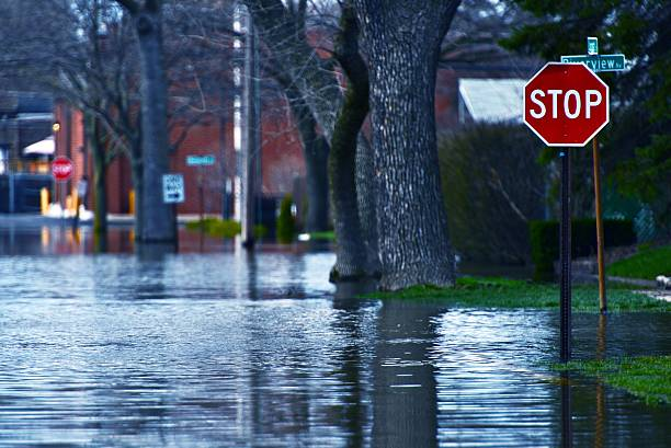 flooded residential street at a stop sign - natural disaster stock pictures, royalty-free photos & images