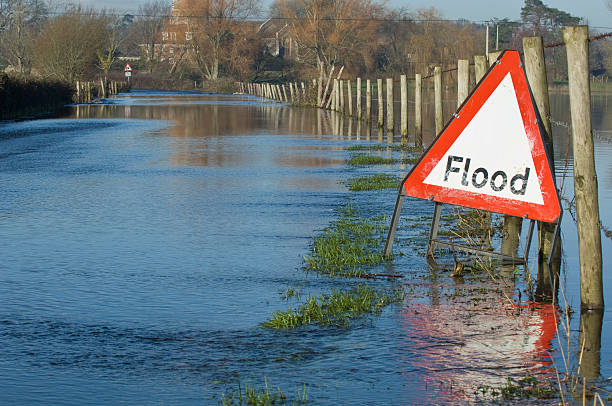 Flooded road and fields A flood warning sign, on a closed country road next to water logged fields in the Avon Valley, Hampshire, England. Flooded after an extreme amount of rainfall at the start of 2014 2014 stock pictures, royalty-free photos & images