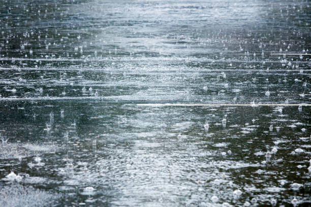 flooded road during heavy rain with raindrops splashes stock photo