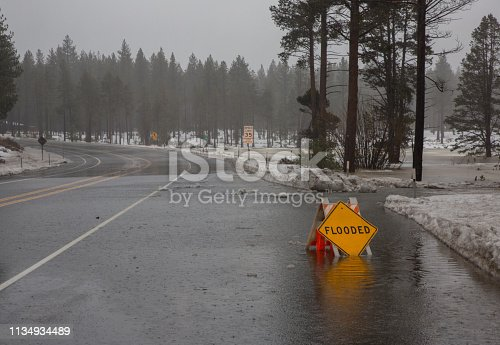 Yellow flooded sign partially submerged in water during a rain on snow event.