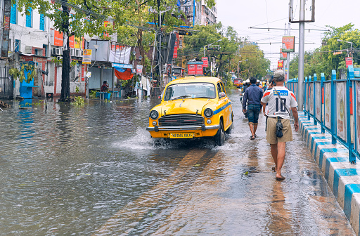 Deshapriya Park, Kolkata, 05/22/2020: Cars passing through flooded city streets, caused by heavy rainfall during storm Amphan. People are seen walking in middle of road, as the pavement is flooded.