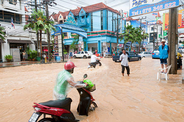 flooded street in patong, phuket, thailand - motorbike, umbrella stock pictures, royalty-free photos & images