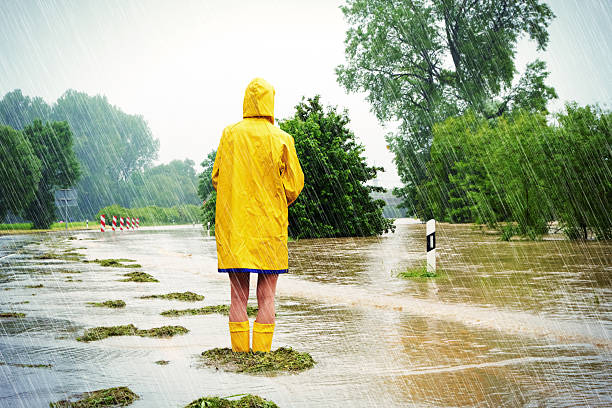 Flooded street Woman standing in a flooded street extreme weather stock pictures, royalty-free photos & images