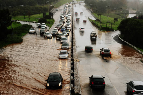 Flooding road Motorists drive through water on a flooding highway extreme weather stock pictures, royalty-free photos & images