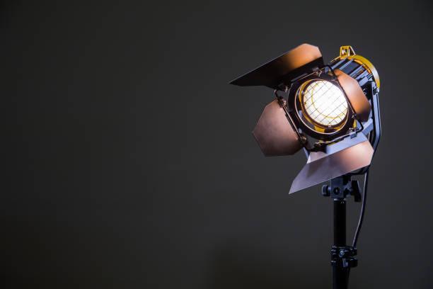 fluter mit halogenlampe und fresnel-linse auf grauem hintergrund. beleuchtungseinrichtungen für das schießen. filmen und fotografieren im inneren - film oder fernsehvorführung stock-fotos und bilder