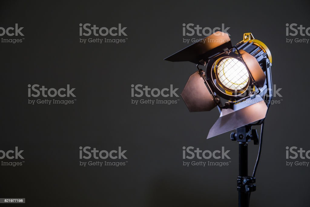 Floodlight with halogen lamp and Fresnel lens on a gray background. Lighting equipment for shooting. Filming and photographing in the interior stock photo