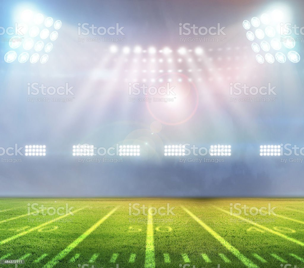 Floodlit, empty football stadium stock photo