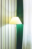 The floor lamp stands against the wall