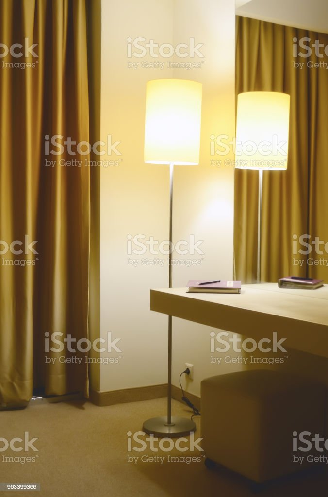 A floor lamp in the corner of the hotel room. A mirror and a console with a notebook and a pen on it - Zbiór zdjęć royalty-free (Architektura)