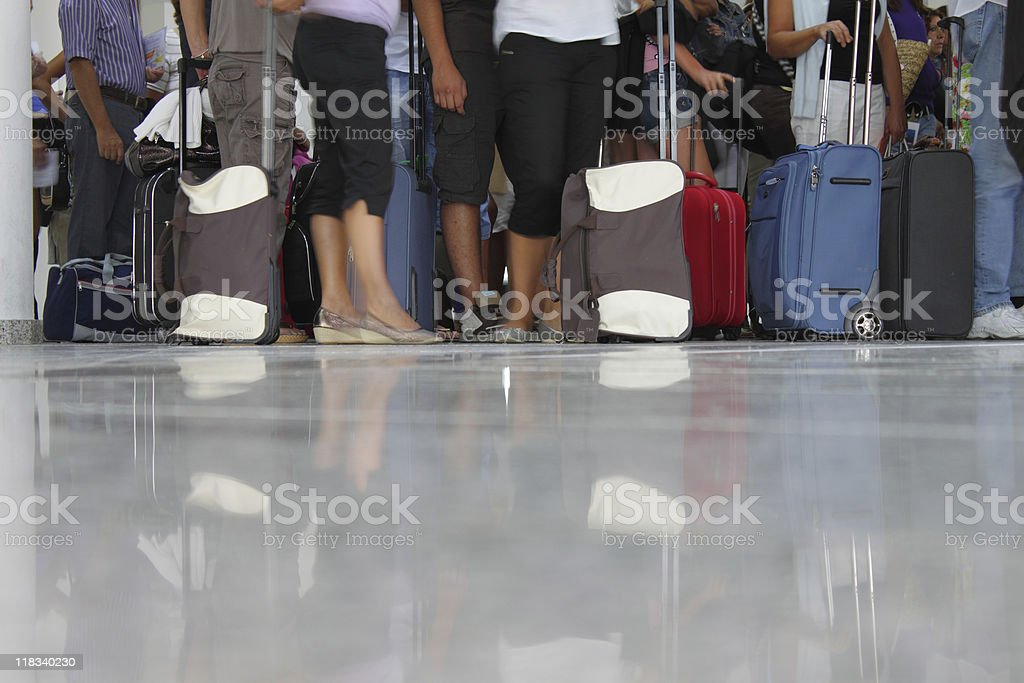Floor level view of people waiting with their luggage stock photo
