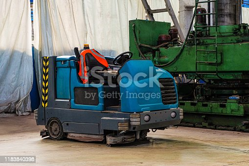 513948652 istock photo Floor sweeper and washer scrubber drier car in an industrial building engineering workshop 1183840398