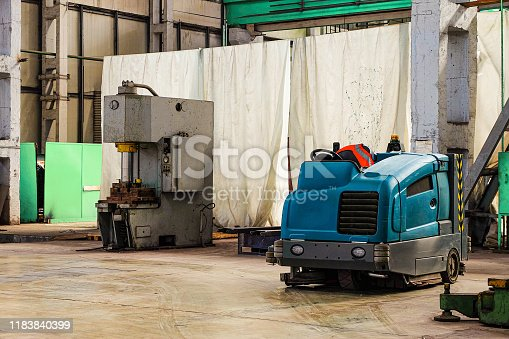 513948652 istock photo Floor sweeper and washer scrubber drier car in an industrial building engineering workshop 1183840399