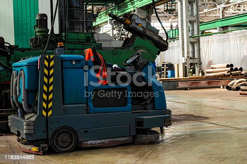 513948652 istock photo Floor sweeper and washer scrubber drier car in an industrial building engineering workshop 1183844983