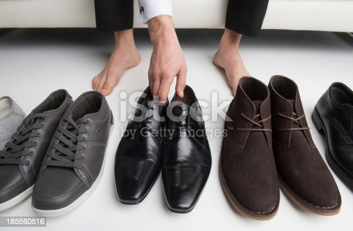 istock Floor view of a man's bare feet choosing from a row of shoes 185560516