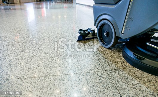 One woman, at home relaxing with her little daughter on the floor, while robot vacuum cleaner is working.