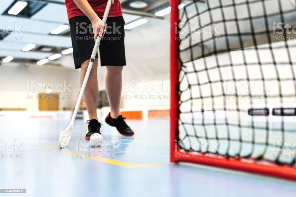 Floorball player training on court. Floor hockey concept. Man running...