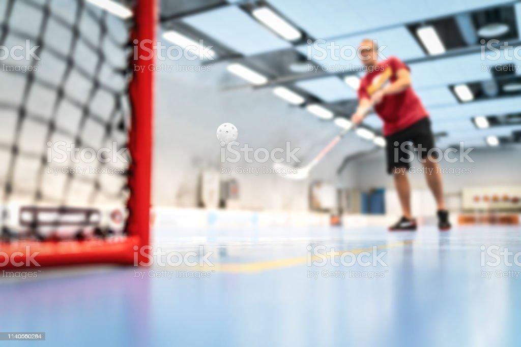 Floorball training on court. Man training floor hockey in arena. Slap...