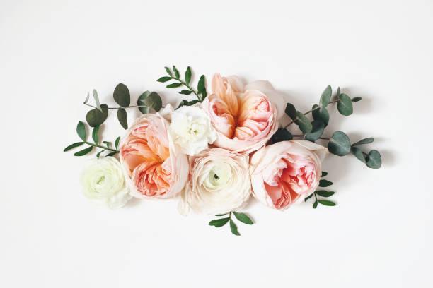 花のアレンジ、ピンクの英語のバラ、ラナンキュラス、カーネーションの花と白いテーブルの背景に緑の葉とウェブバナー。フラットレイ、トップビュー。結婚式や誕生日スタイルのストッ� ストックフォト