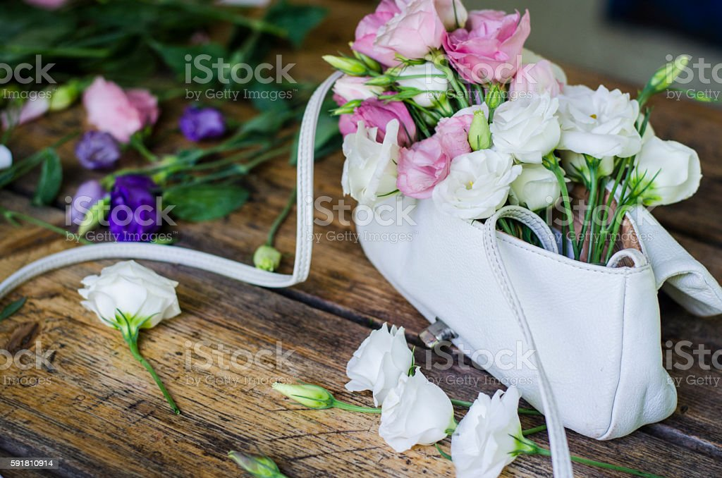 Floral background. Beautiful flowers in a handbag. stock photo