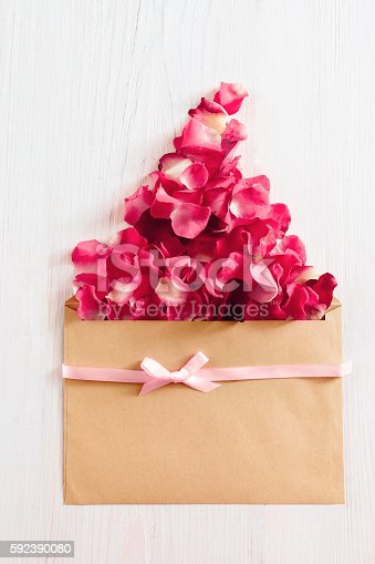 680461500 istock photo Floral background with envelope and rose petals 592390080