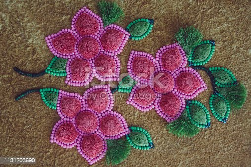 Pink beaded flowers and moose hair tufting on leather with green leaves