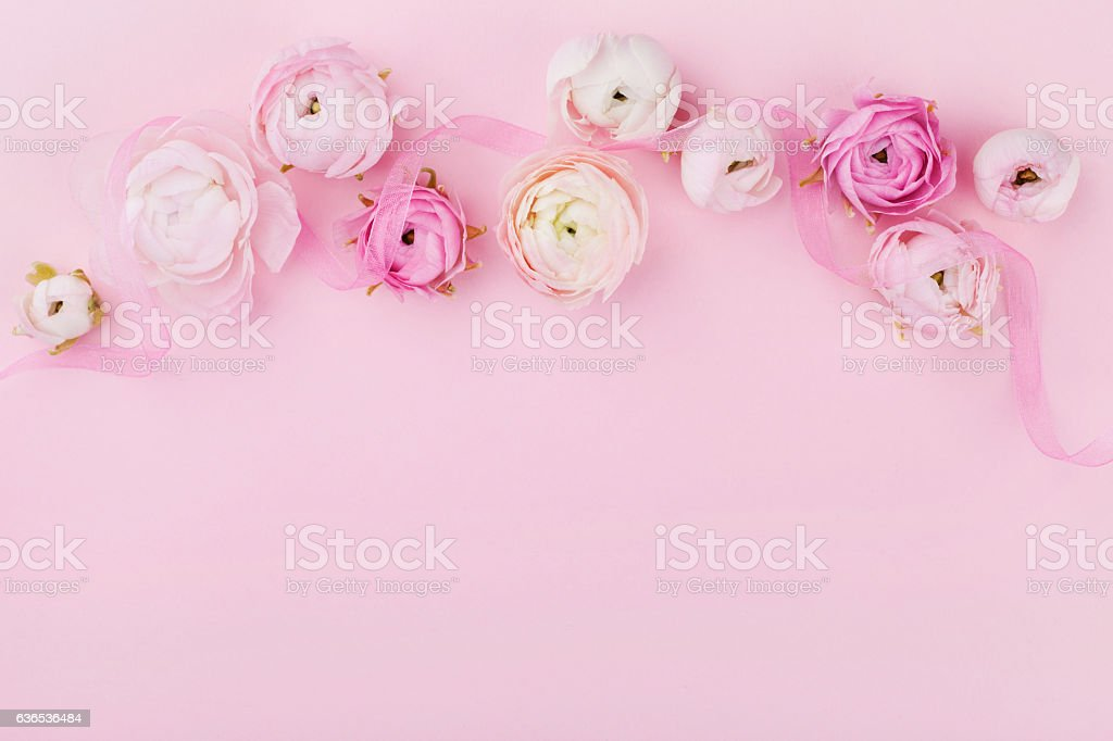 Floral border in flat lay style on pink desk. Copyspace.