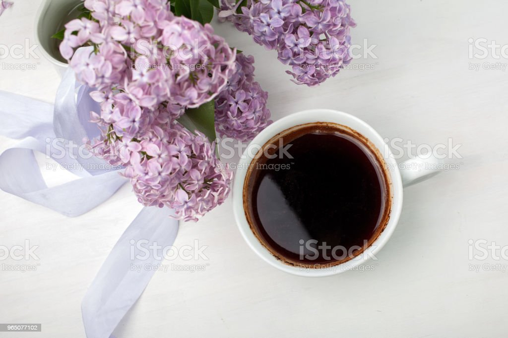 Floral composition made of beautiful purple lilac on white wooden background with cup of coffee. royalty-free stock photo