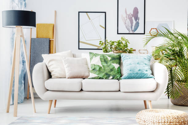 Floral cushion on beige sofa Floral cushion on beige sofa and paintings on wall in living room with pouf, lamp and plant cushion stock pictures, royalty-free photos & images