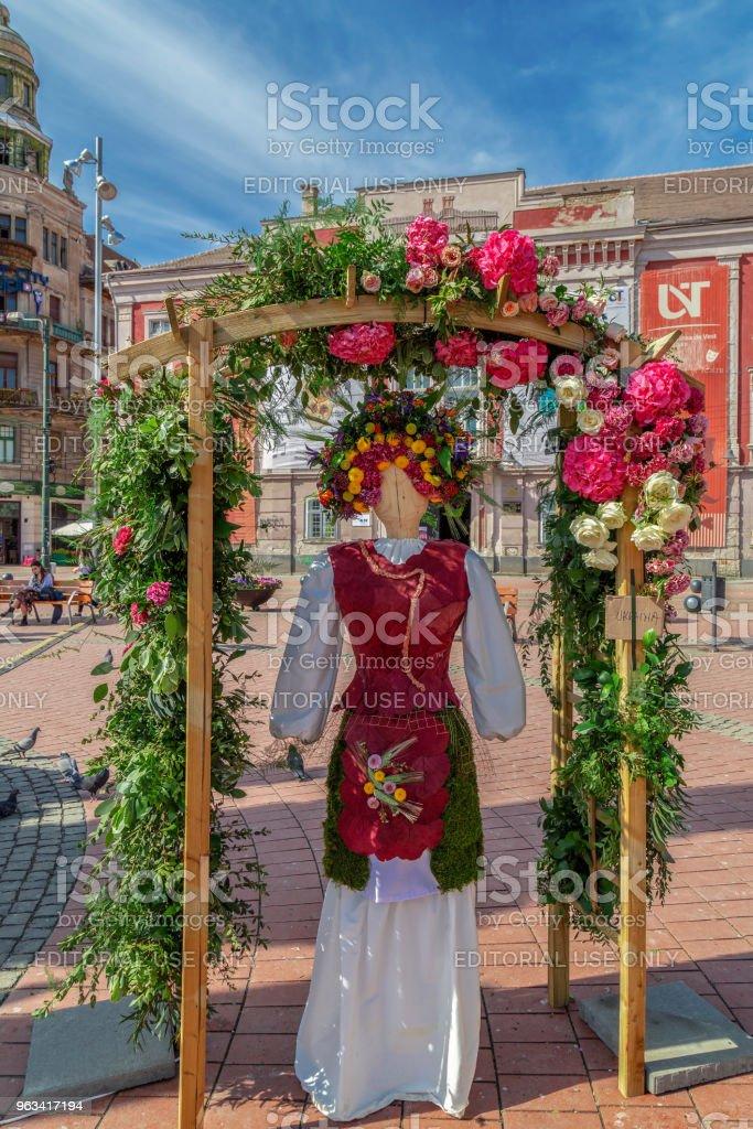 Décoration florale avec une statue en bois, vêtu d'un costume populaire fait de fleurs - Photo