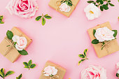 istock Floral frame composition with roses and gift box on pastel pink background. Flat lay, top view. Valentines day 1070488802