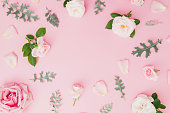 istock Floral frame made of pink and white roses with leaves on pastel pink background. Flat lay, top view. 1071690024