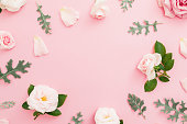 istock Floral frame made of roses and leaves on pastel pink background. Flat lay, top view. 1084456514