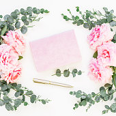 istock Floral frame of pink roses and eucalyptus with pink notebook and pen on white background. Flat lay, top view 844589524
