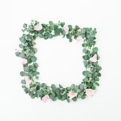 istock Floral frame of pink roses flowers and eucalyptus branches on white background. Flat lay, top view 1094273740