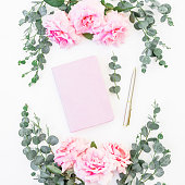 istock Floral frame of rose flowers and eucalyptus branches with notebook and pen on white background. Flat lay, top view 831167866
