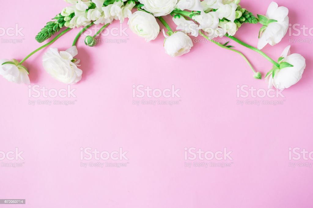 Floral frame of white flowers - ranunculus and snapdragon on pink...