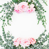 istock Floral frame with pink roses and eucalyptus branches on white background. Flat lay, top view 835506088