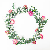 istock Floral frame with pink roses flowers and eucalyptus branches on white background. Flat lay, top view 1127713922