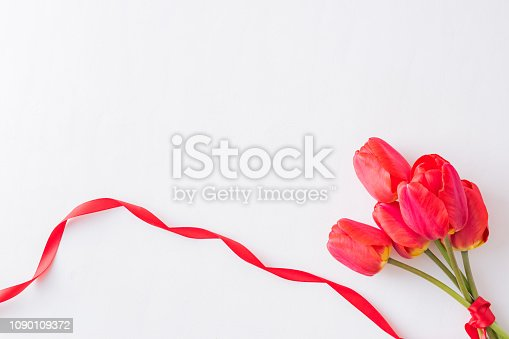 Floral frame with red tulips on a light background. Flat lay, top view
