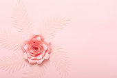Floral greeting card on pink background. Pastel paper flowers flat lay, top view