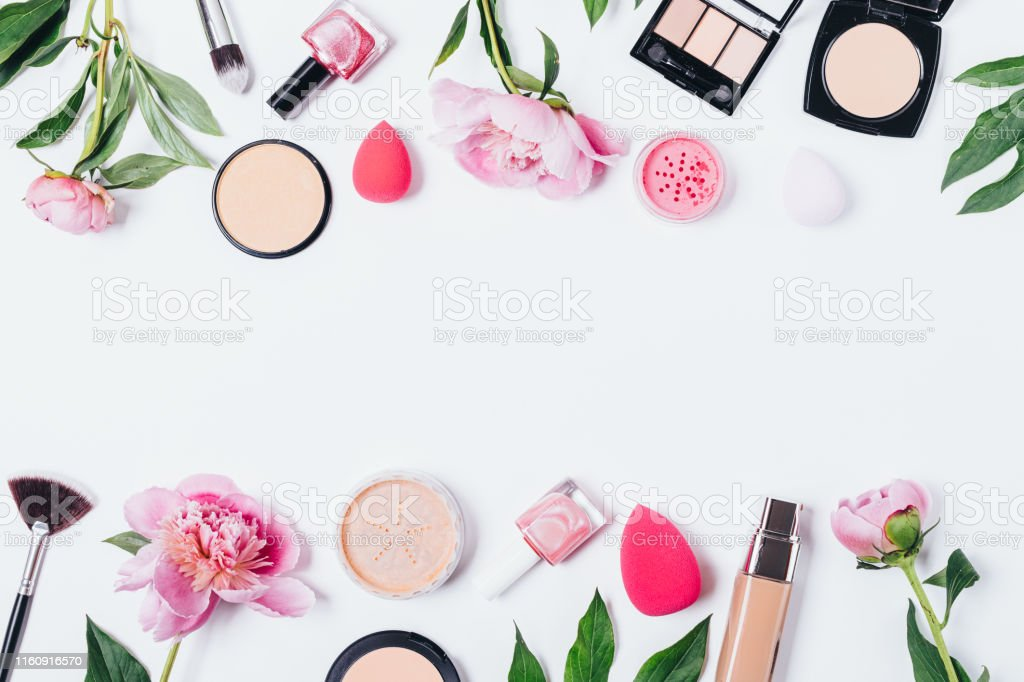 Floral makeup background of peonies next to cosmetic products and...