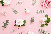 istock Floral pattern made of roses and leaves on pastel pink background. Flat lay, top view. 1069095778