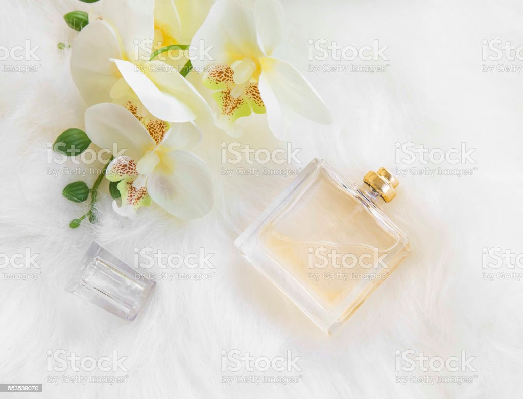 Floral perfume bottle with yellow orchid, overhead shot stock photo