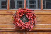 Floral red outdoor Christmas wreath hanging at entrance door
