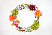 istock Floral round crown (wreath) with flowers and leaves. Flat lay, top view. Creative arrangement with roses, gray grefsheim leaves, sevenbark and waterlily. 827021210