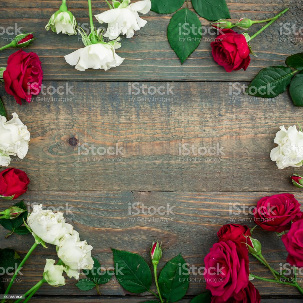 Floral round frame of red and wood roses isolated on wood background....