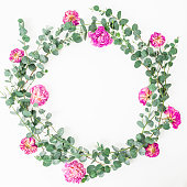 istock Floral round frame. Rose flowers and eucalyptus branches on white background. Flat lay, top view 830682964