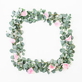 istock Floral wreath frame with rose flowers and eucalyptus branches on white background. Flat lay, top view 835507928